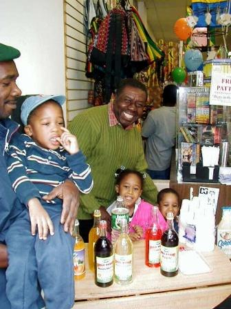 Oliver Samuels is all smiles as he samples the popular Jamaican Pure Bulk Syrup.  Joining Oliver l-r are Timex, and their little friends Andy, Melissa, and Stephen.  Jamaican food. Caribbean food. Oliver Samuels.